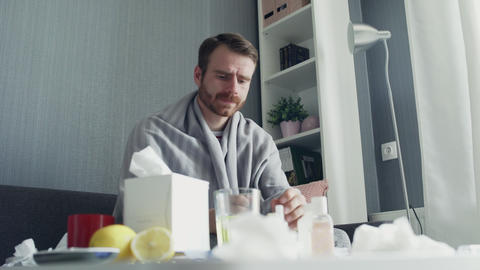 Sick man pouring medication or antipyretic syrup to spoon and drinking it GIF