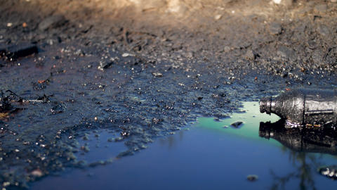 4k dolly video of plastic bottle lying in black oil or diesel waste pubble on Live Action