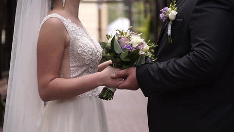 wedding, close up, bride and groom join hands with a wedding bouquet Live Action
