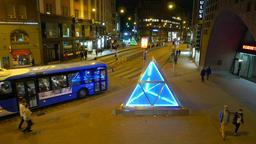Empty Helsinki street at night, bright blue pyramid from glass, street turn Footage