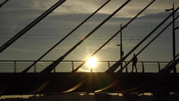 Boy come along cable stayed bridge handrails, silhouette view, bright sun spot Footage
