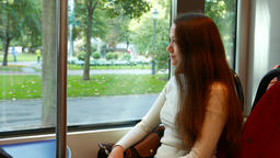 Young thoughtful woman sit in Helsinki tram, look out, vehicle begin move Footage