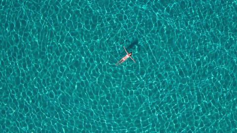 Aerial - Rotating and raising above beautiful young woman floating on water Footage