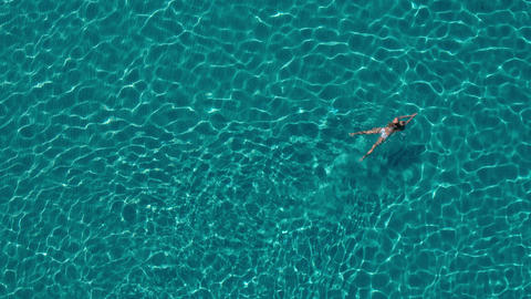 Aerial - Young woman in white bikini swimming in crystal clear water Footage