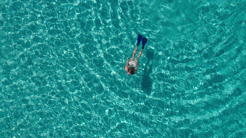 Aerial - Young woman snorkeling underwater in crystal clear waters Footage
