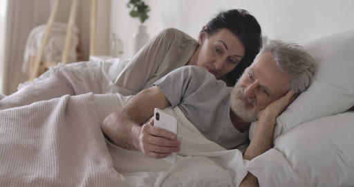 Suspicious senior Caucasian wife looking over husband's shoulder at smartphone Live Action