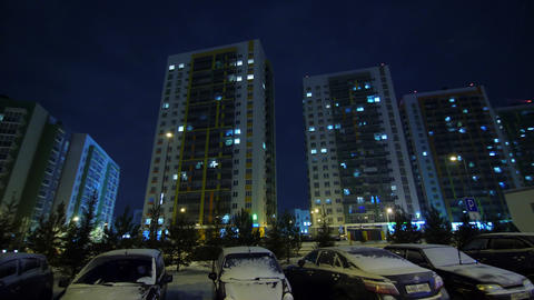 apartment buildings with windows on street at winter night GIF