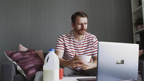 Shocked man having breakfast and using a laptop to terrible read news GIF