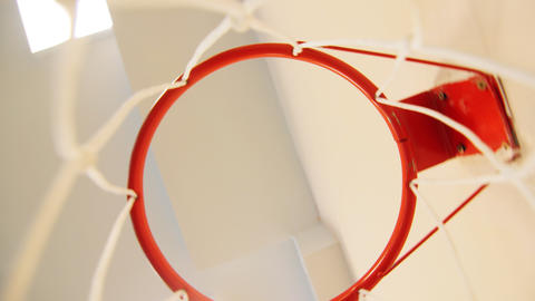 camera turns fast under red basketball hoop with white net GIF