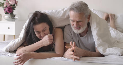 Portrait of positive senior Caucasian couple lying in bed under blanket Live Action