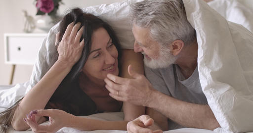 Close-up portrait of smiling senior Caucasian couple lying under white blanket Live Action