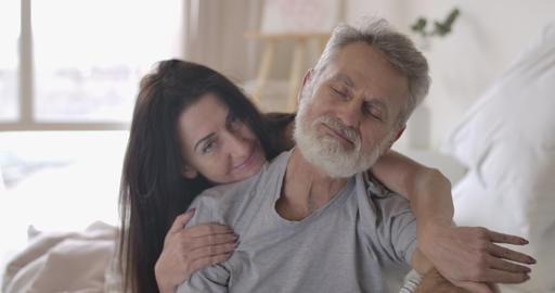Brunette senior Caucasian woman hugging handsome grey-haired husband. Mature Live Action