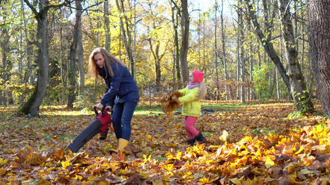 naughty child girl making leaves fight with gardener mother in autumn yard GIF