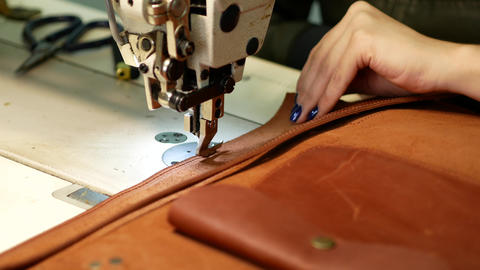 Seamstress sews leather bag in a sewing workshop. Woman operates sewing machine Live Action