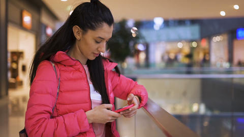 Close view of smiling girl using phone waiting in the mall Live Action