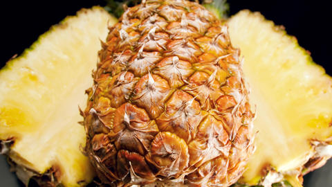 Closeup 4k video of pineapple cut in slices lying on black background. Perfect Live Action