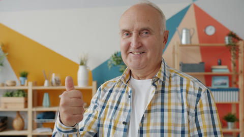 Portrait of handsome elderly man showing thumbs-up hand gesture in apartment Live Action