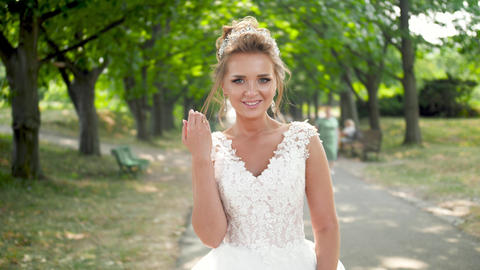 4k video of happy smiling young bride walking on long alley in park and smiling Live Action