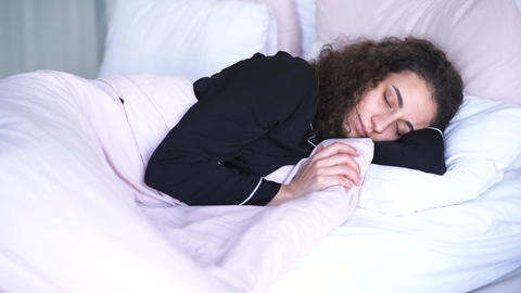 Curly-haired brunette girl sleeping and smiling. Portrait of happy calm Live Action