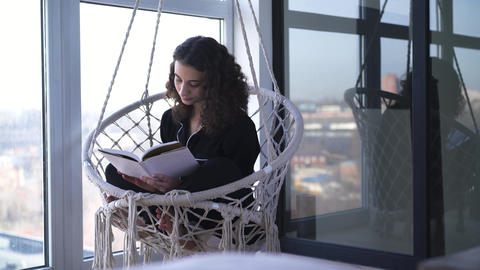 Young Caucasian woman sitting in hanging armchair and reading book. Portrait of Live Action