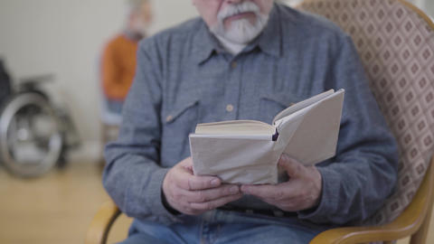 Concentrated unrecognizable old Caucasian man reading literature in nursing home Live Action