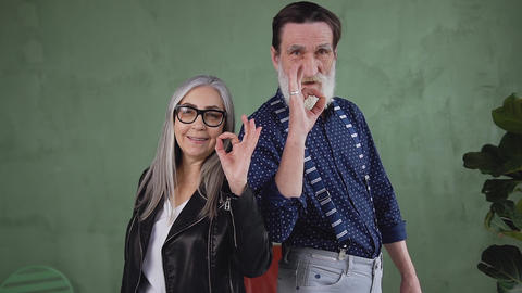 Appealing friendly satisfied senior man and woman posing on camera and showing Live Action