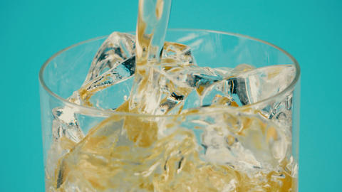 Pouring lemonade into a glass with ice cubes against cyan background, close-up Live Action