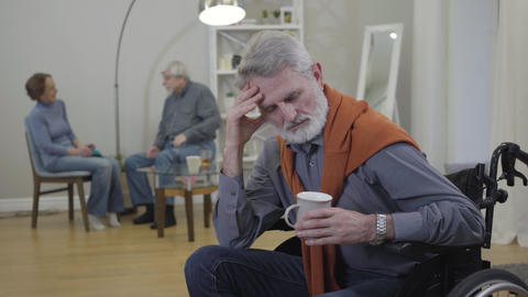 Exhausted senior Caucasian man in wheelchair rubbing temples as positive nursing Live Action