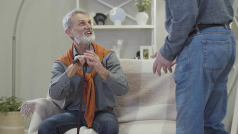 Handsome positive Caucasian old man greeting friend indoors. Happy male retiree Live Action