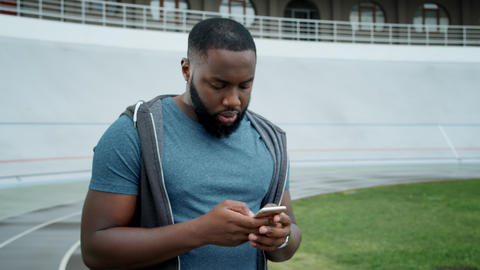 Athlete using smartphone at stadium. Sportsman texting message on smartphone Live Action