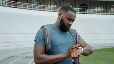 Jogger using smart watch at stadium. Man tracking bad results after workout Live Action