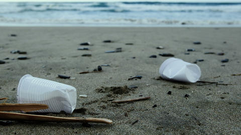 Plastic glasses trash on sandy sea shore waves motion,polluted nature,cilento Live Action