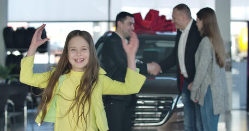 Cheerful little Caucasian girl and adult people at the background showing thumbs Live Action