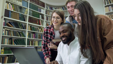 Attractive cheerful modern multiethnic friends working over home task in the Live Action