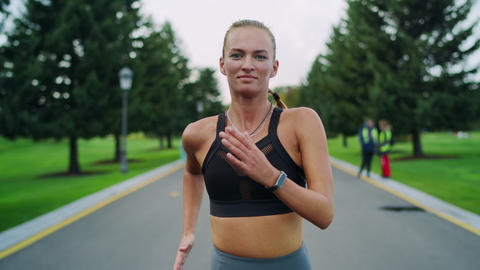 Happy athletic woman jogging in park. Girl doing cardio workout outdoors Live Action