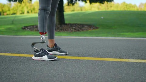 Woman with prosthetic leg standing on road.Athlete legs preparing to run in park Live Action