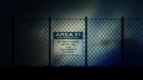 Zoom in into an Area 51 Sign on a Metal Fence on a Stormy Night Footage