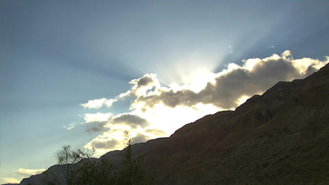 Sun on a Top of a Mountain Behind Clouds in Time Lapse Footage