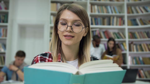 Pretty calm concentrated young woman in glasses reading book in the university Live Action