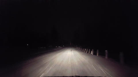 Driving While Snowing on Rural Road at Night. Driver Point of View POV Snow and Snowflakes During Live Action
