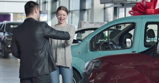Positive Caucasian businesswoman taking car keys and making victory gesture in Live Action