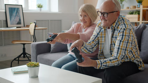 Slow motion of happy old people playing video game at home enjoying leisure fun Live Action