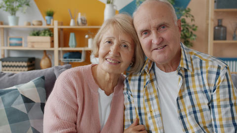 Portrait of happy family elderly husband and wife smiling relaxing on couch in Live Action