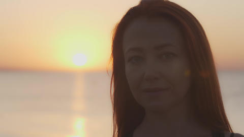 Portrait of a woman against the background of dawn over the sea GIF