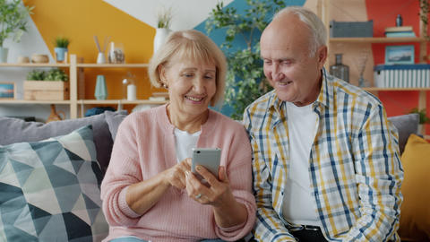 Old woman using smartphone touching screen relaxing on couch with senior husband Live Action
