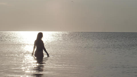 A beautiful woman in a swimsuit stands in the middle of a calm sea at dawn. The Live Action