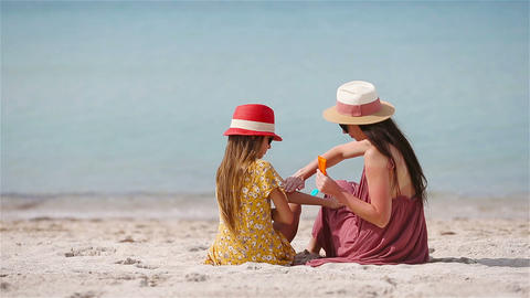 Young mother applying sun cream to daughter nose on the beach. Sun protection Live Action