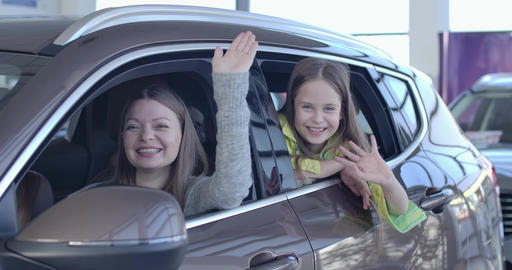 Positive Caucasian mother and daughter waving from new elegant black car in Live Action