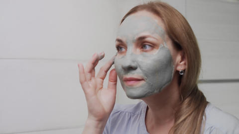 Close up of Adult woman applying clay mask on her face looking at the camera Live Action
