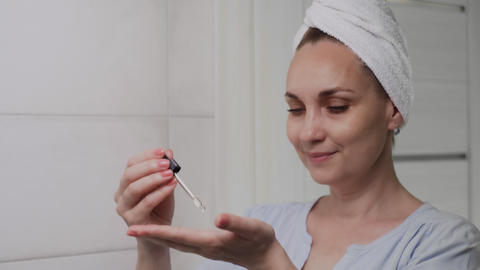 Adult with a towel on her head woman applying lotion or oil and looking in Live Action